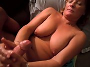 Mature wife using both her arms to stroke the cock squeezing it rigid